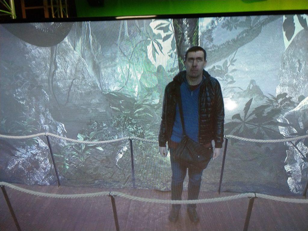 Dominik vor dem Green-Screen, der einen Dschungel mit Riesenschlange zeigt.