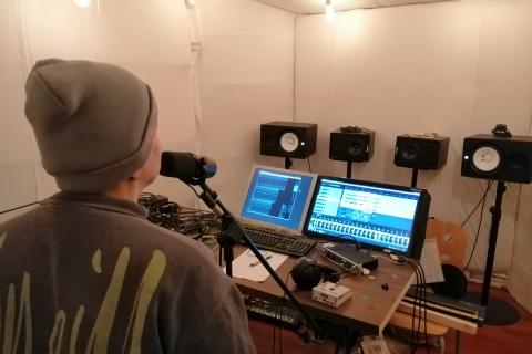 Die TeilnehmerInnen der Band haben im Proberaum/Tonstudio ein Lied aufgenommen