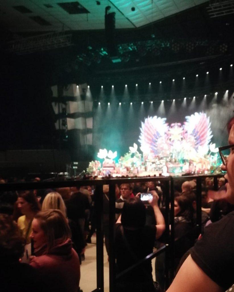 Blick auf die Bühne, von der Rollstuhlrampe aus gesehen. Kunstvoll mit Blumen gestaltetes Bühnenbild.